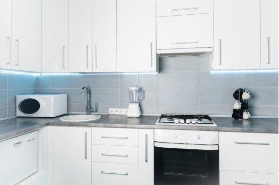 Белая глянцевая кухня с серой столешницей
